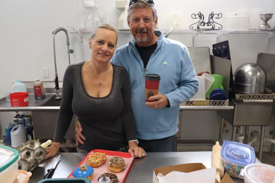 Owners Alysa and Grady Watkins show off a tray of their doughnuts and coffee.