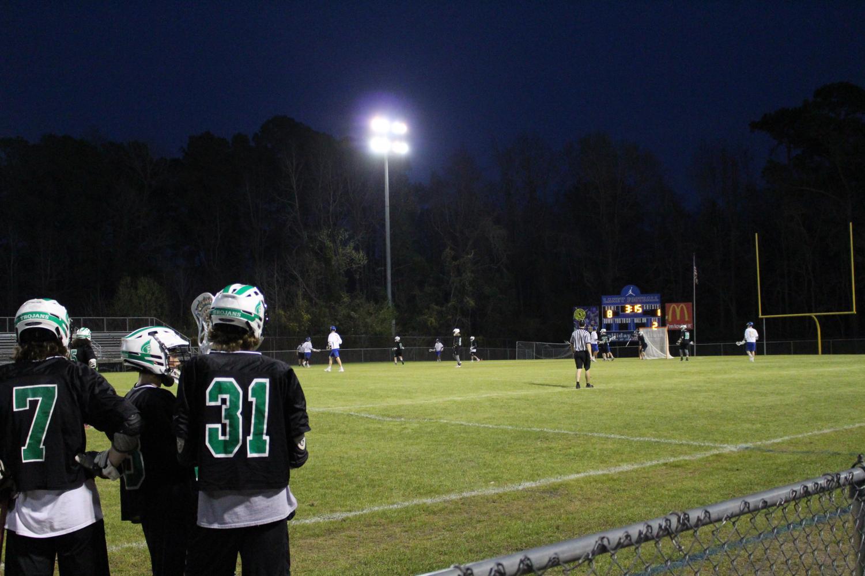 Men's Lacrosse players look on as their team plays defense.