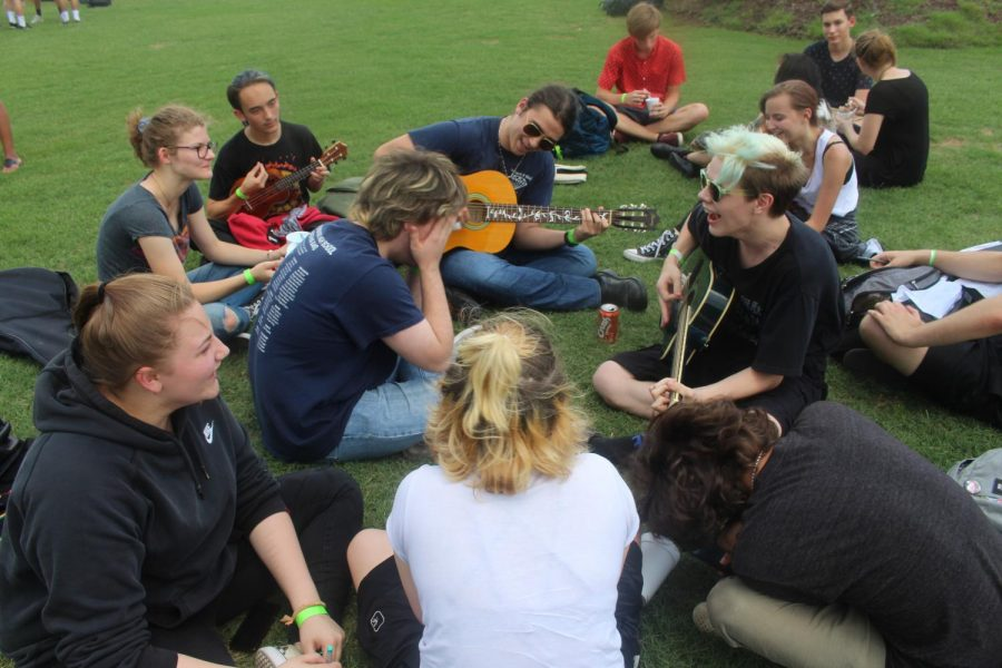 Students play tunes with their guitars on the lawn.