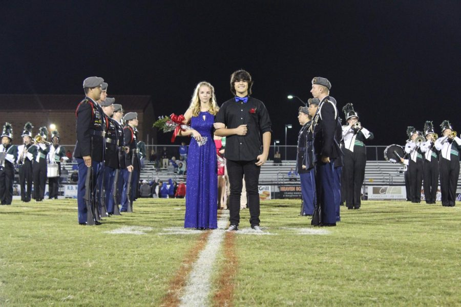 Junior candidates Breanna Trudeau and William Pickard strut across the football field as they