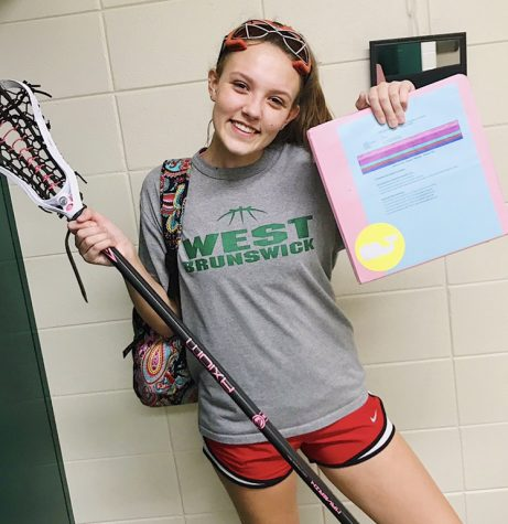 Sophomore Lacrosse Player, Elizabeth Norfleet poses for the camera with her lacrosse equipment and binder.