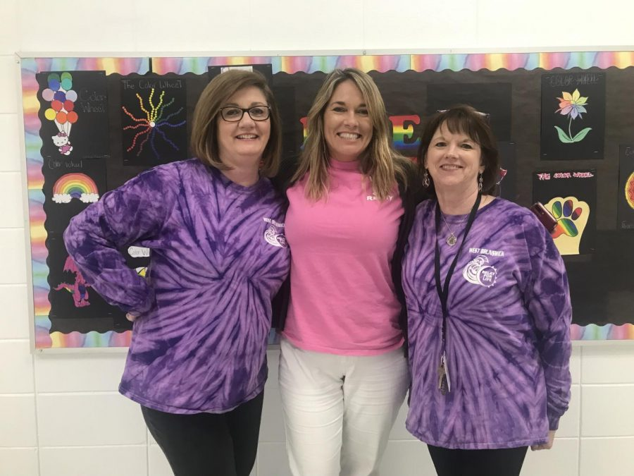Teachers pose in the hallway as a group with their relay shirts.