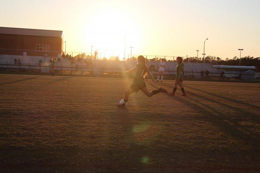 Senior+Greer+Jocelyn+kicking+the+ball+across+the+field.