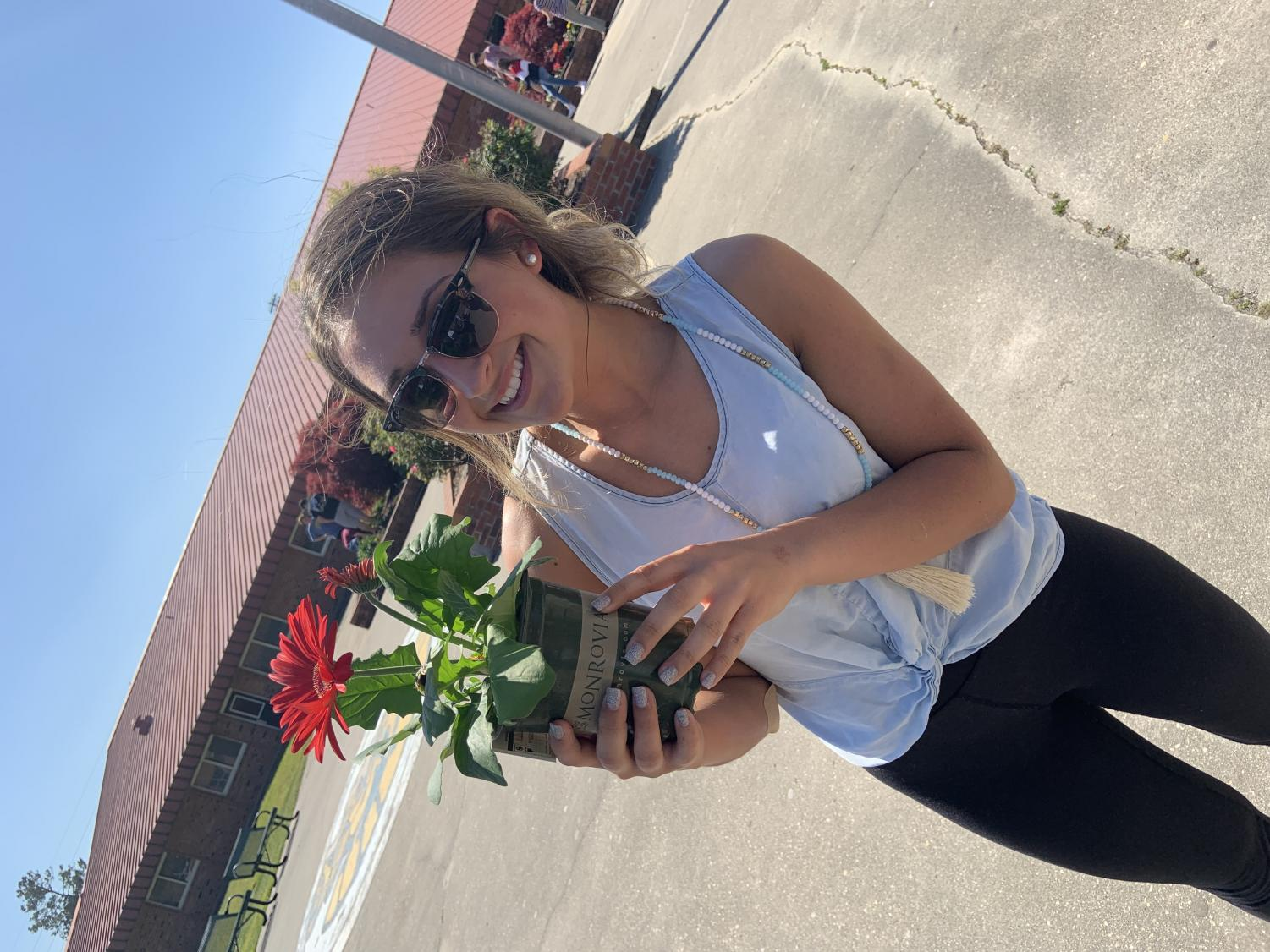 Senior Chloe Lach represents Key Club by helping plant flowers.