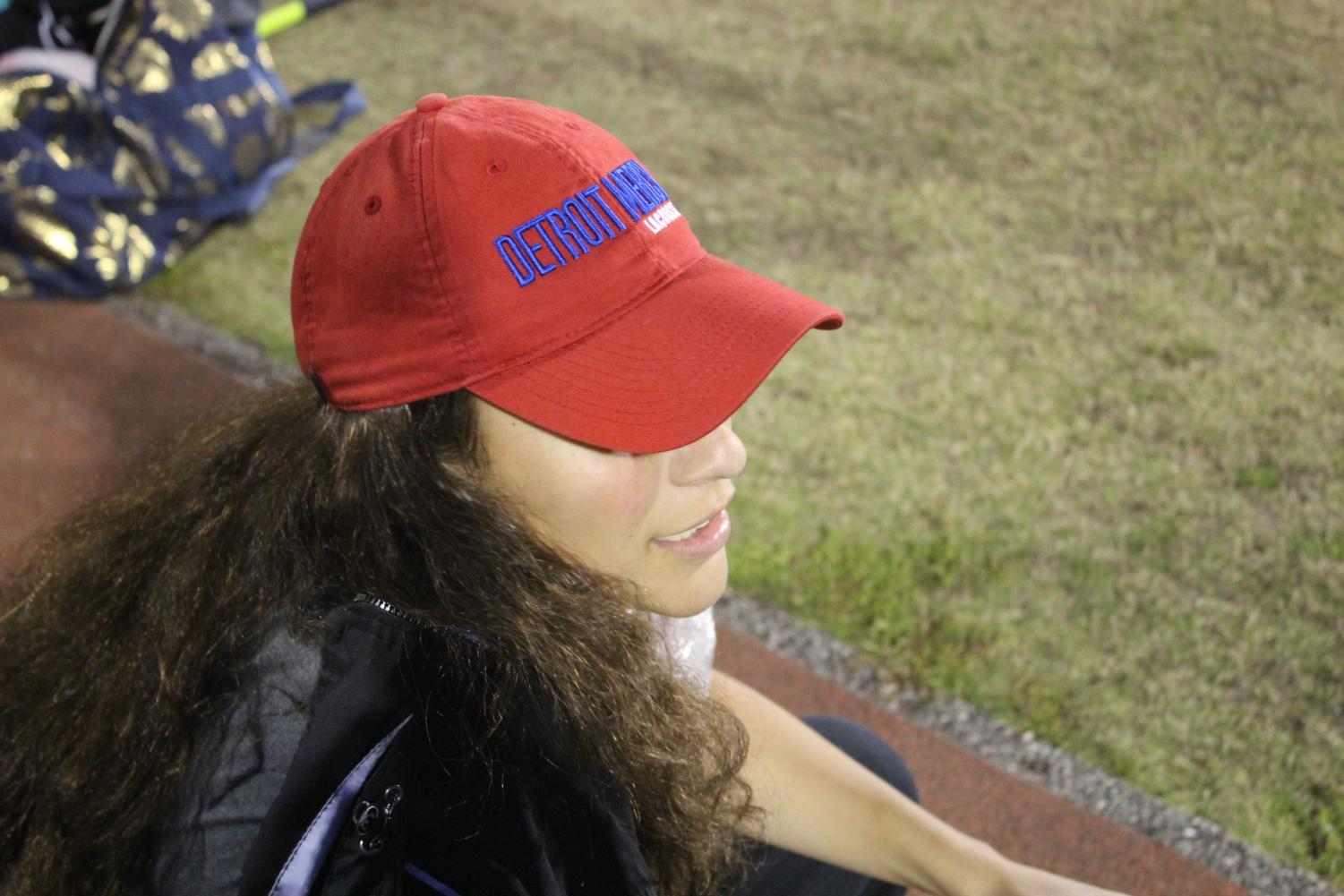 Cecelia Vergara represents her college as she watches the women's lacrosse game.