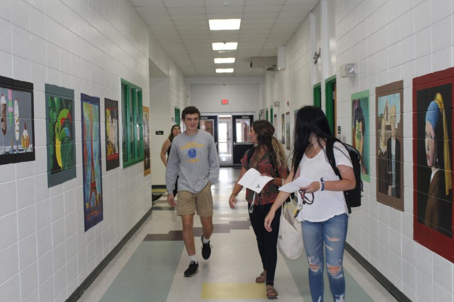 Connor Gushman, Rayna Gunther, and Chloe Lach walking through the hallways without a care in the world.