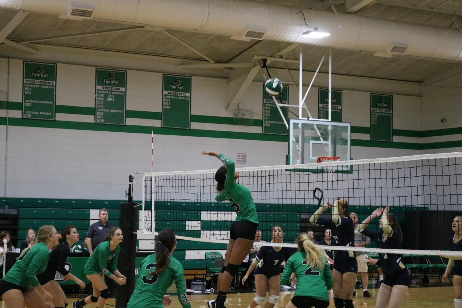 Kayden+Cupid%2C+a+freshman+on+the+team%2C+jumping+up+to+hit+the+ball.