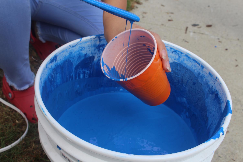 A close up of Kayla Ward pouring a beautiful shade of royal blue paint.