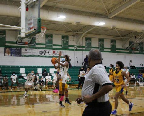 Varsity player, JJ Cobb jumps up to make a basket.