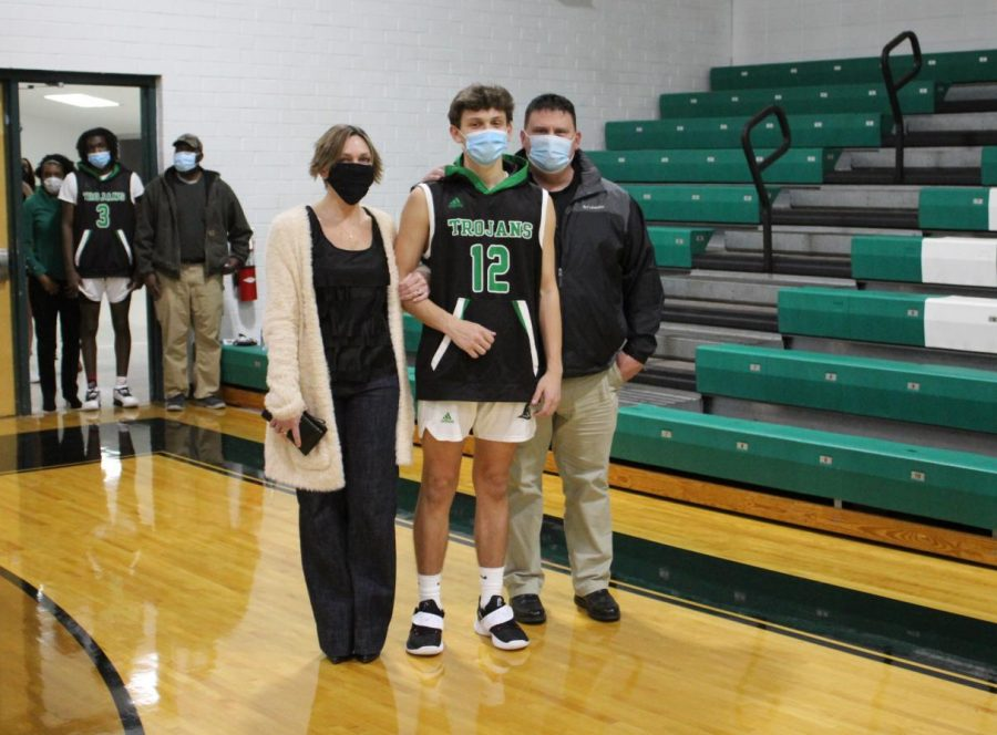 Senior basketball player, Cole Hamilton, is escorted by his parents.