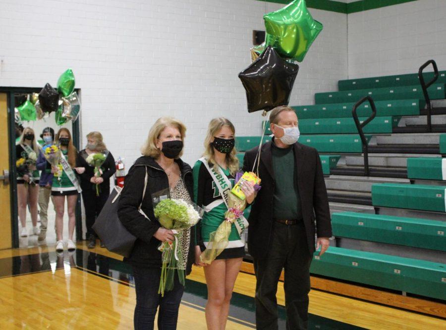 Senior cheerleader, Caroline Bryant, is escorted by her parents.