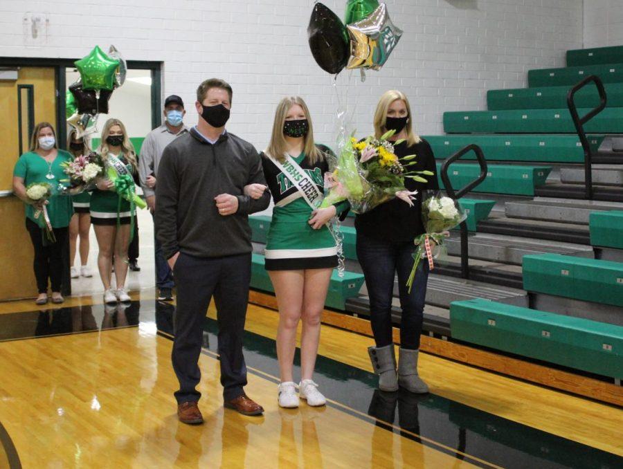 Senior cheerleader, McKenzie Pope, is escorted by her parents.