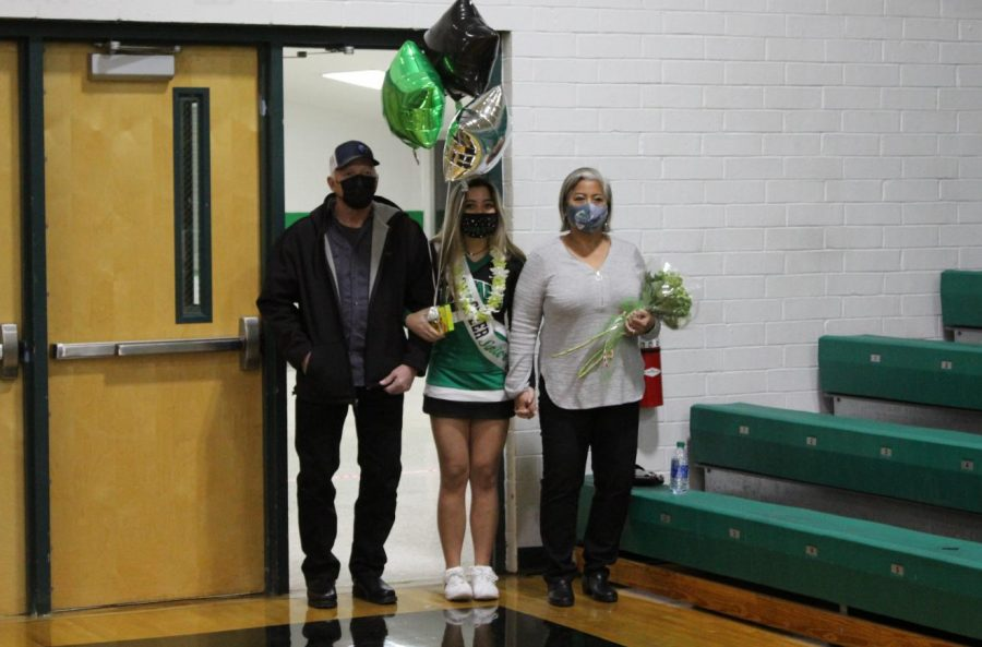 Senior Lily Wells is escorted by her parents.
