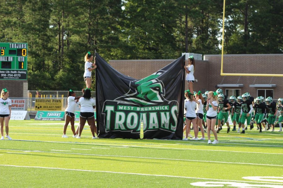 The West Brunswick Cheer Team welcomes the Trojan JV Football Team with a banner before the game.