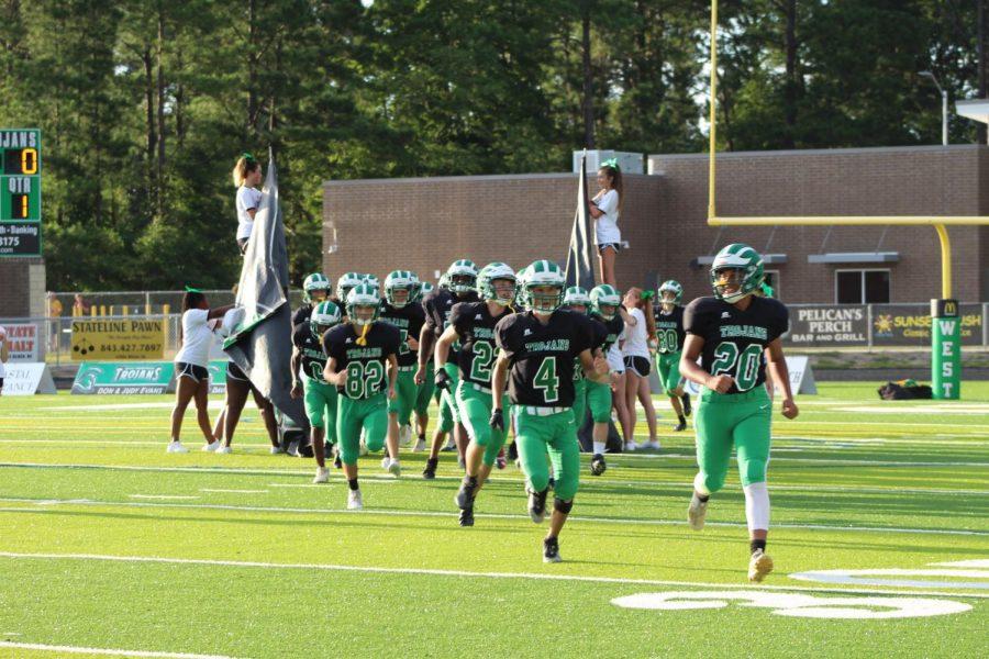 The Trojan Football Team runs through the Trojan banner before the game.