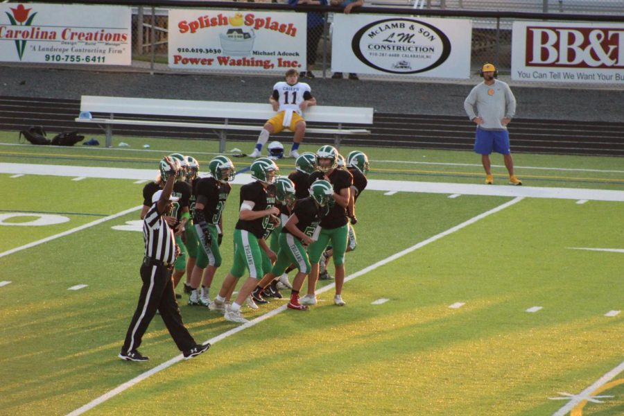 The Trojans huddle together to prepare for the next play.