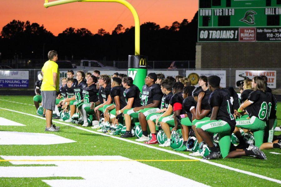 The Trojans listen to Coach Hickman after the game.